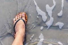 Нога мужчины с темповыми сальто сальто носки пока стоящ на пляже стоковые фото