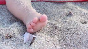 Нога младенца в песке моря сток-видео