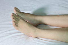 Нога на белой кровати Стоковое Изображение