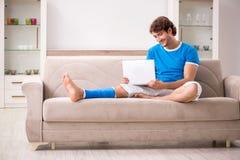Нога повредила молодого человека на софе стоковое изображение rf