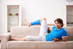 Нога повредила молодого человека на софе стоковое фото rf