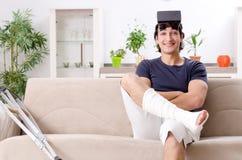Нога повредила молодого человека страдая дома стоковая фотография rf
