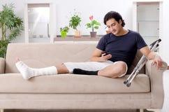 Нога повредила молодого человека страдая дома стоковая фотография