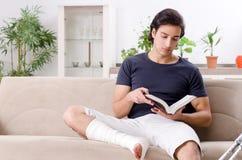 Нога повредила молодого человека страдая дома стоковое фото