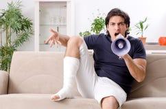 Нога повредила молодого человека страдая дома стоковое фото rf