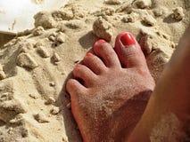 Нога с красными ногтями в песке на пляже стоковые изображения