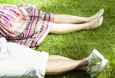 Нога человека и женщины на траве, друге и концепции отношения Стоковое Изображение
