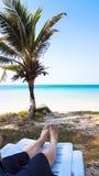 Нога ` s девушки кладет на белое кресло в пляже Стоковое Изображение