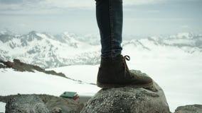Ноги авантюриста в кожаном ботинке stomps на утесе на взгляде снежной горы сценарном сток-видео