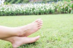 Ноги азиатской женщины ослабляя на поле травы Стоковые Изображения RF