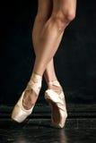 Ноги балерины конца-вверх в pointes на черноте Стоковые Фотографии RF