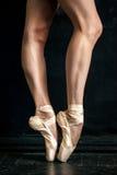 Ноги балерины конца-вверх в pointes на черноте Стоковое Фото