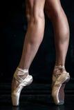 Ноги балерины конца-вверх в pointes на черноте Стоковые Фото