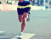 Ноги бегуна на дороге города в гонке марафона идущей Стоковые Изображения RF