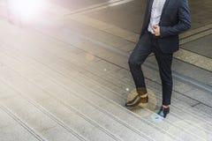 Ноги бизнесмена носят шагать черного костюма идя вверх лестница в современном городе, дело растет вверх и концепция успеха Стоковое Фото
