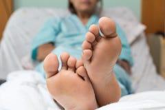 Ноги больного молодой женщины ослабляют в кровати Стоковые Фото