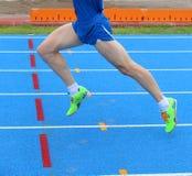 ноги быстрого бегуна бегут в в следе атлетики Стоковая Фотография RF