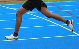 ноги быстрого бегуна бегут в синь в следе атлетики Стоковое Изображение RF