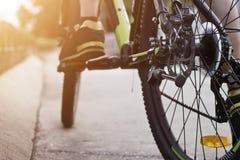 Ноги велосипедиста на велосипеде на улице в предпосылке захода солнца Стоковая Фотография RF