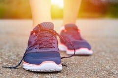 Ноги в ботинках спорт идущих с развязанными шнурками на дороге пока jogging Концепция образа жизни и здоровья спорт Стоковое фото RF