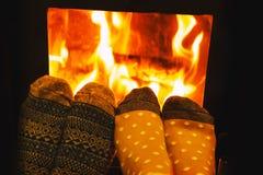 Ноги в носках шерстей любовников пар грея уютным огнем Стоковые Изображения