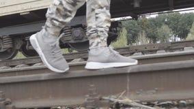 Ноги в тапках и брюках защитного идут на рельсы сток-видео