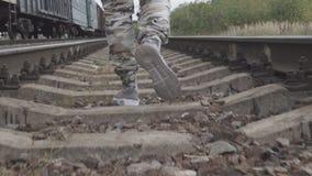 Ноги в тапках и брюках защитного идут на рельсы видеоматериал