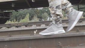 Ноги в тапках и брюках защитного идут на рельсы акции видеоматериалы