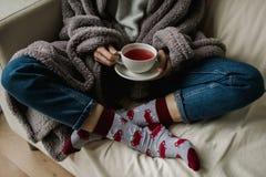 Ноги в шерстяных носках Женщина расслабляющая с чашкой горячего питья и нагревать ее ноги в шерстяных носках Стоковое Изображение