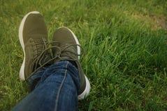 Ноги голубых джинсов Backpacker женщины наслаждаются взглядом на поле лета зеленой травы Стоковое Изображение