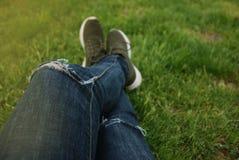 Ноги голубых джинсов Backpacker женщины наслаждаются взглядом на поле лета зеленой травы Стоковое Фото