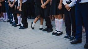 Ноги девушек в белом гольфе и мальчиков в брюках костюма стоят в линии на следе школы 1-ого сентября 1-ое сентября - линия школы стоковые изображения rf