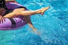 Ноги девушек играя с водой в бассейне стоковое изображение
