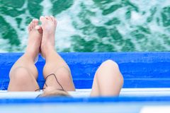 Ноги девушки висят с шлюпки пассажира края в океане Посмотрите верхнюю часть Стоковые Фото