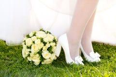 Ноги девушки или невесты в белых ботинках с смычками и круглым букетом свадьбы Стоковое Изображение RF