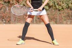 Ноги девушки спортсмена около ракетки тенниса Стоковое фото RF