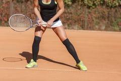 Ноги девушки спортсмена около ракетки тенниса Стоковые Изображения