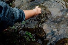 Ноги детей касаются воде создавая пульсации Знак надежды и детства счастья Мальчик 2-3 лет старого стоковое фото rf