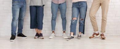 Ноги друзей Молодые люди в джинсах и брюках стоковая фотография