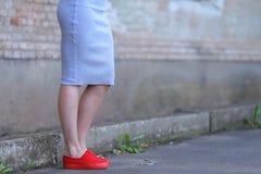 Ноги девушки в красном цвете выскальзывани-на на предпосылке бетонной стены Стоковое Изображение