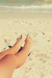 Ноги девушки в песке на пляже Стоковое Фото