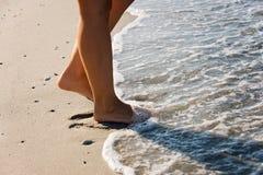 Ноги девушки идя в море развевают Стоковые Изображения