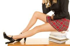 Ноги девушки школы сидят на книгах Стоковые Изображения RF