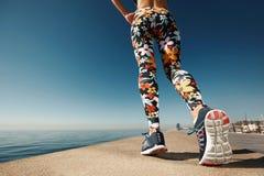 Ноги женщины бегуна бежать на крупном плане дороги на ботинке Стоковая Фотография RF