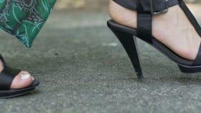Ноги женщины ботинок высокой пятки идут вперед в замедленное движение, идут бетон города даты сток-видео