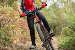 Ноги женщины велосипедиста ехать горный велосипед Стоковая Фотография