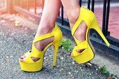 Ноги женщины в желтых сандалиях с солнечным светом Стоковые Изображения
