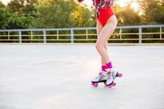 Ноги женщины в купальнике катаясь на коньках на коньках ролика outdoors Стоковое Изображение