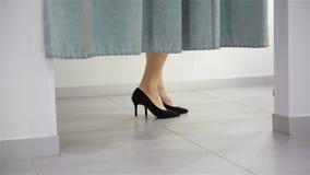Ноги женщины в примерочной в торговом центре Покупки и концепция магазина одежд Близкий поднимающий вверх взгляд накрененной высо сток-видео