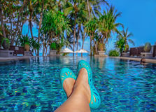 Ноги женщины лежа вниз на sunlounger рассматривая вода Стоковые Фото